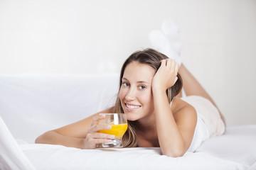 Woman in Bed drinking orange juice at breakfast