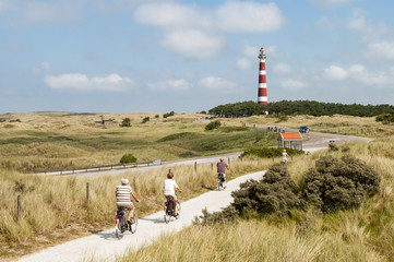 Seniors riding on bicycles in the dunes of Ameland near the lighthouse, Netherlands