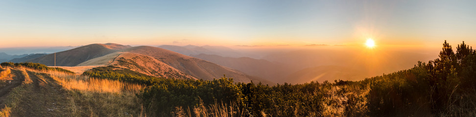 Panorama of amazing sunrise on mountain ridge
