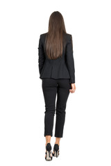Elegant woman in business black suit walking away. Rear view isolated