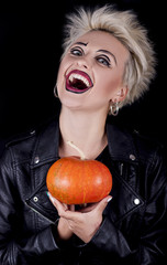 extravagant blonde with a frightening grin with a pumpkin in the