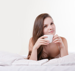 Woman on her bed smiling while holding a cup of coffee