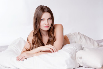 Beautiful woman relaxing on bed, bedtime in morning