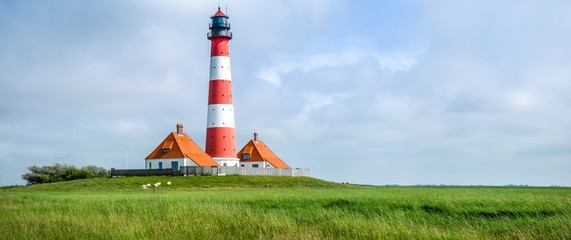 Garden Poster Lighthouse Traditional lighthouse at North Sea with blue sky and clouds