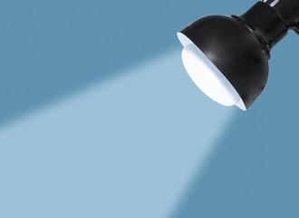 Black metal desk lamp head, bright blue light bulb and beam