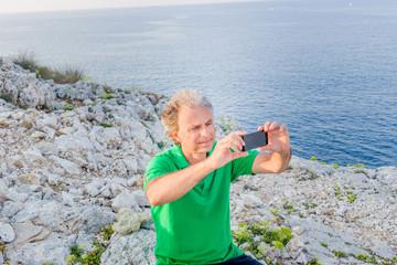 Handsome man takes a selfie in seaside town