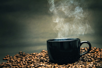 still life of warm black cup of coffee on  roasted coffee beans