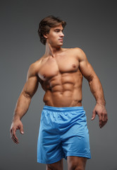 Strong muscular bodybuilder showing his body.