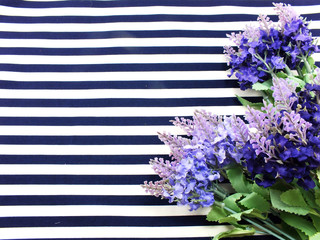 arrangement of artificial lavender flowers bouquet located on Blue and white stripes