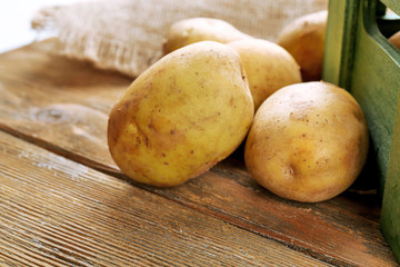 Young potatoes on wooden table close up