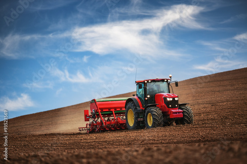 Fototapete Farmer with tractor seeding crops at field