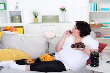 Dicke Frau isst Schaumküsse auf dem Sofa