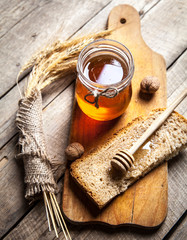 Honey in a jar, slice of bread, wheat