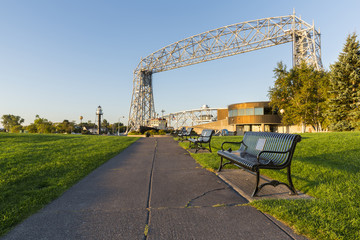 Duluth Canal Park / A sidewalk with park benches leading towards a lift bridge, lighthouse, and tug boat.