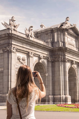 "Young blonde woman taking photos of the ""Puerta de Alcala"" in Madrid with her smart-phone."
