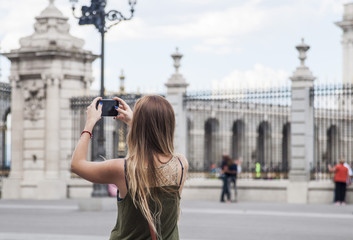 Young blond woman sightseeing and taking pictures near the Royal Palace in Madrid.