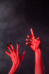 Scary red devil hands with black nails
