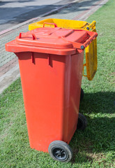 two orange and yellow color litter bins in garden at midnoon