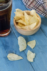 potato chips and cola in glass  on wooden table.