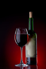 Wine and glass against a black background with red light