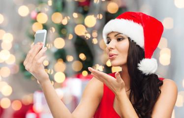 woman in santa hat taking selfie by smartphone