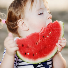 Cute girl kid at countryside eating big watermelon.