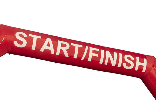 A Red start and finish line inflatable banner isolated against white a background. Banner was marking the start of a 5K run but could be used for any purpose.