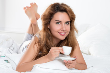 Young woman laying on her bed with a cup of coffee