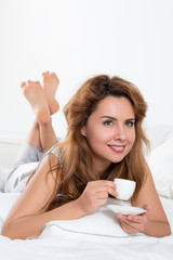 Young woman laying at her bed with a cup of coffee