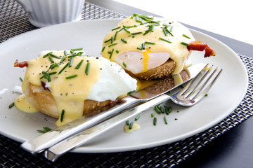 Elegant breakfast consists of eggs Benedict on a toasted bun with bacon and delicious hollandaise sauce