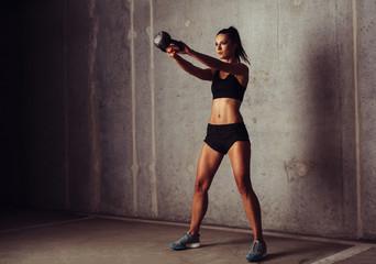 Slim attractive sportswoman in a kettlebell training