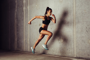 Slim attractive sportswoman running against a concrete background