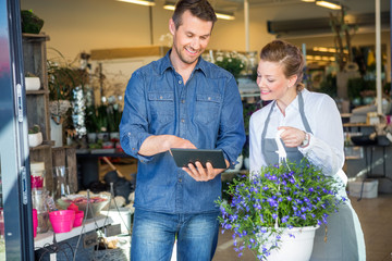 Customer Using Digital Tablet While Standing By Florist