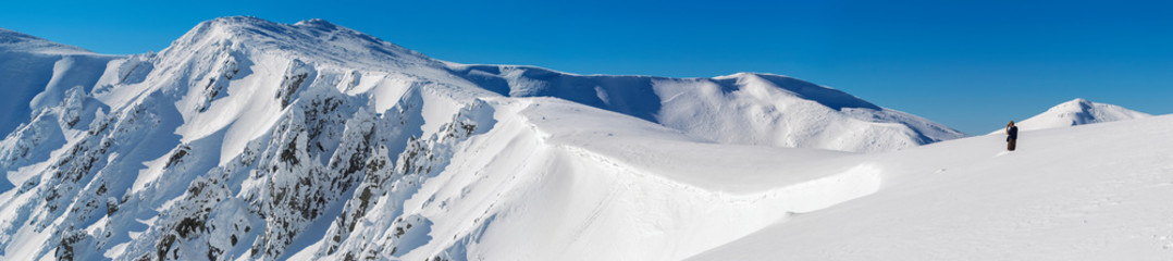 Panorama of snow-covered rocks of the mountain range. A man standing in the snow at the edge of the slope. The sky is clear, sunny. Winter. Ukraine