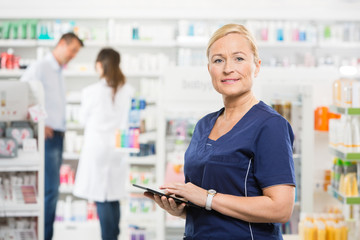 Confident Assistant Holding Tablet Computer At Pharmacy
