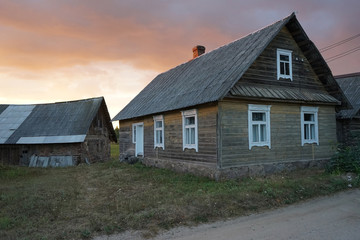 old wooden house in the village against sunset