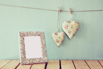 image of blank frame and hanging fabric hearts on rope in front of wooden background. retro filtered image