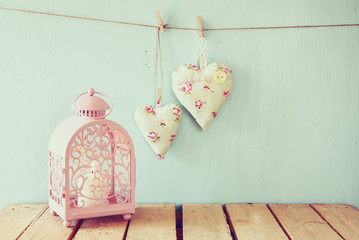 vintage pink classical frame, fabric hearts hanging on the rope and lantern with garland lights, on wooden table. retro filtered image