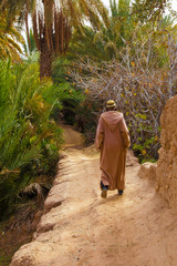 Local Moroccan man wearing a traditional robe walks on a dirt path into an oasis