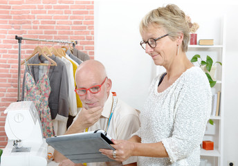 middle aged couple in a sewing workshop with tablet