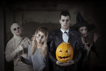 Portrait of a mummy, zombie, witch and a vampire with a carved pumpkin