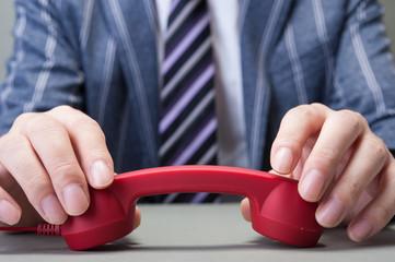 赤い受話器を持つ男性の手