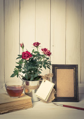 Retro photo frame and old pen with roses bouquet on wooden board