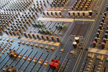 Faders and knobs on professional musical mixer