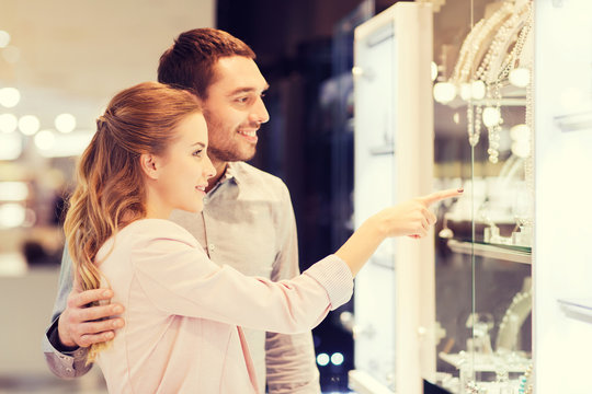 couple looking to shopping window at jewelry store