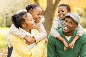 Portrait of a young smiling family in piggyback