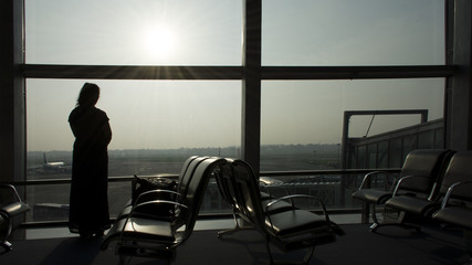 Woman standing at the Airport Window
