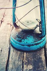 Detail of Vintage Dirty Blue kerosene Lamp on Wooden Background