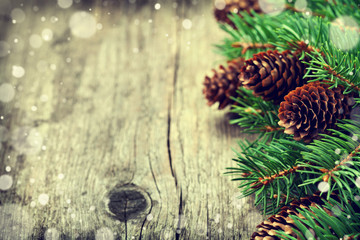 Christmas card of fir tree and conifer cone on rustic wooden background, snow effect, copy space for text, vintage toning