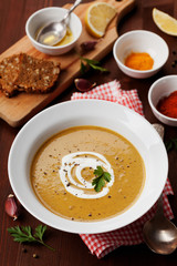 Lentil cream soup in a bowl with spices turmeric, paprika and garlic on wooden table